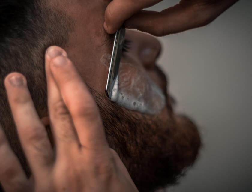 Person holding a razer shaving a man's beard