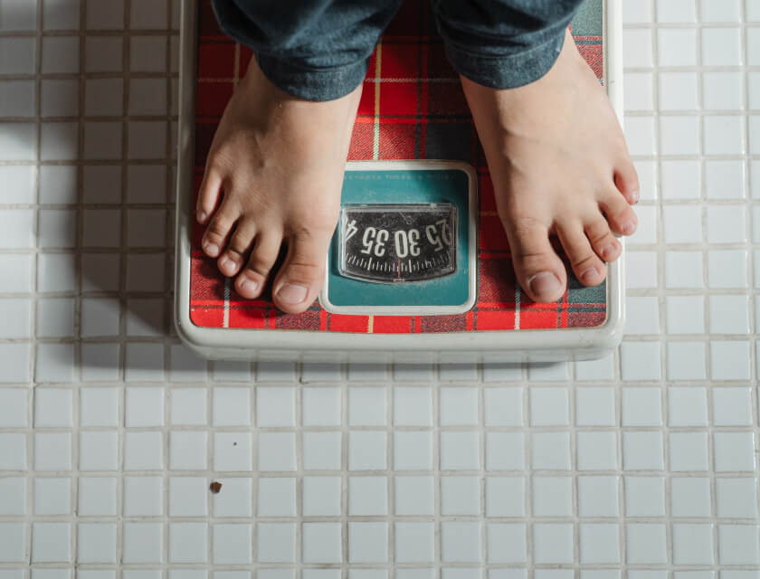Macro of bare feet standing on a traditional bathroom scale