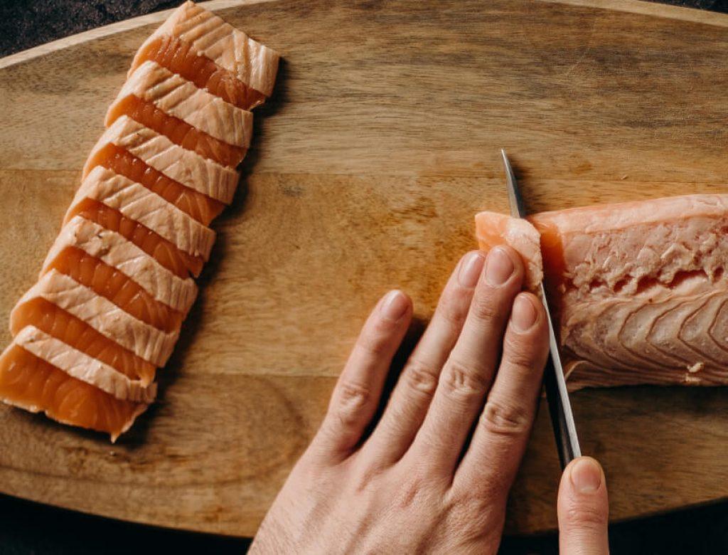 Sheff chopping raw fish on wooden chopping board
