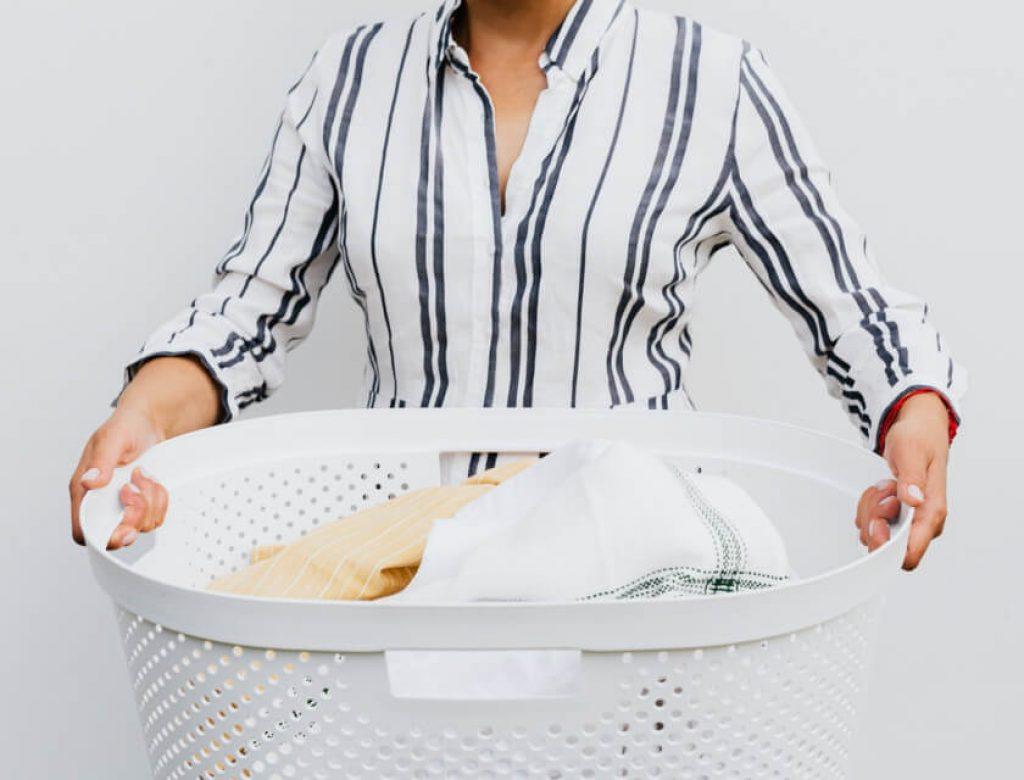Woman in white and black stripe shirt holding white plastic basket full of laundry