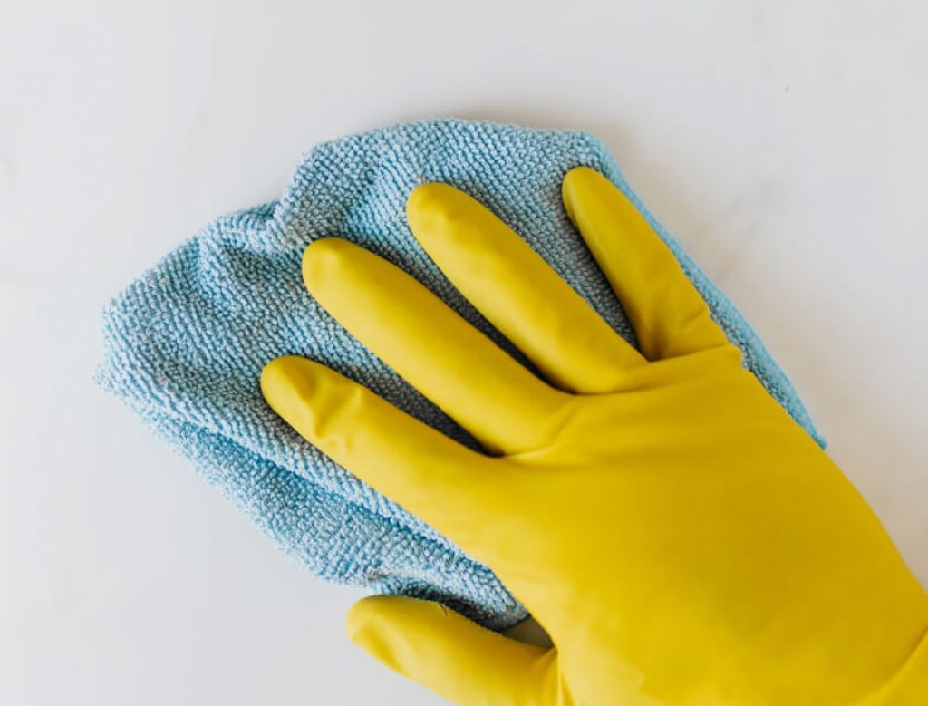 Close up of yellow cleaning glove holding a blue microfiber cloth