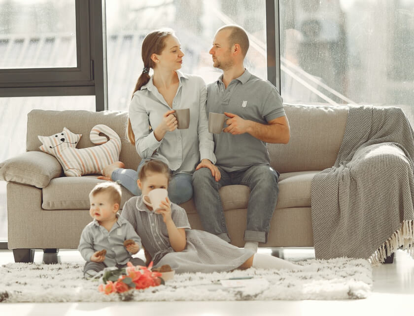Happy family with two kids resting on sofa at home