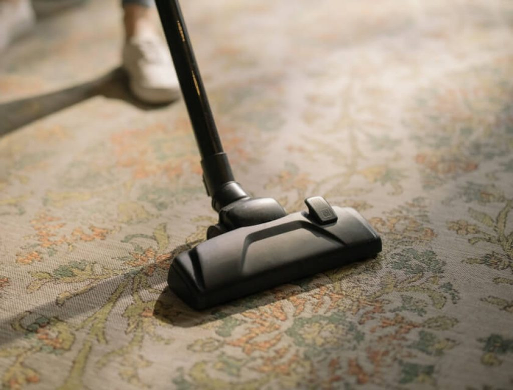 Black vacuum cleaner on a brown and white rug close up